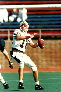 Joe Moorhead throwing football as quarterback for Fordham Rams.