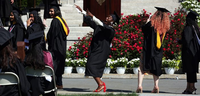 Woman holding up her diploma