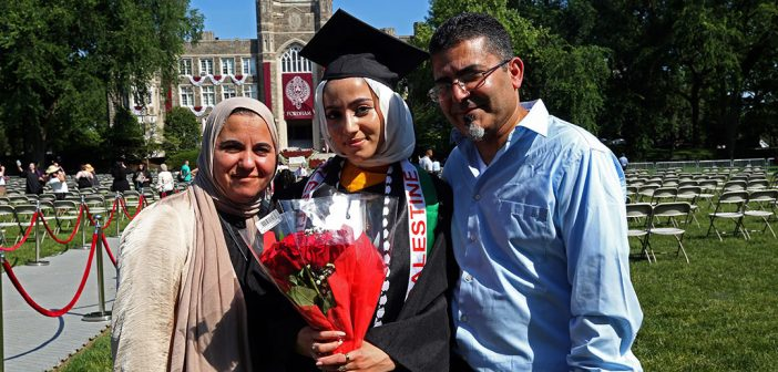 Woman with her parents posing for a picture in fromt of Keating Hall
