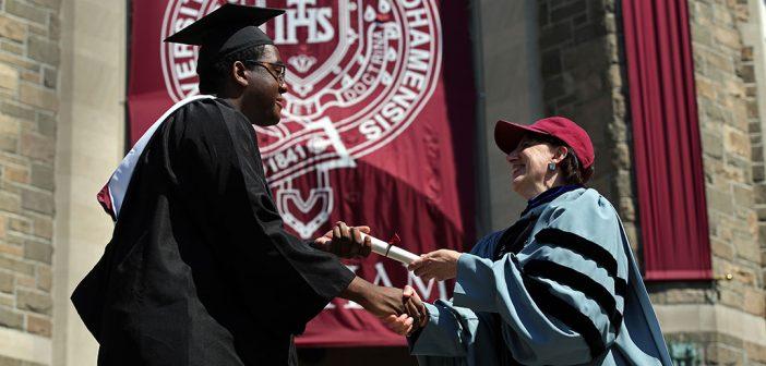 Dean Laura Auricchio giving a diploma to a graduate