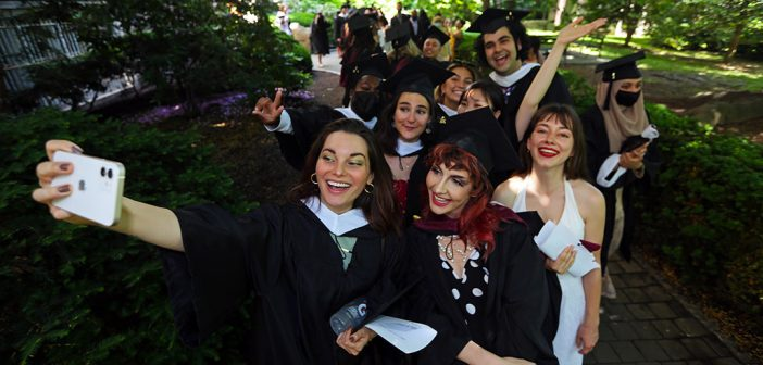 Several gradautes smile for a mass selfie