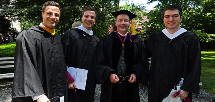 Four male graduates stand together for a photo
