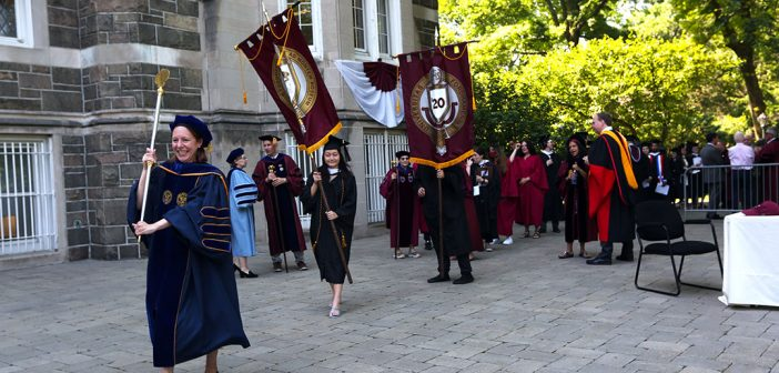 Graduates process across Keating Terrace with banners
