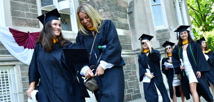 Two women wearing black graduation gowns smile while they walk.