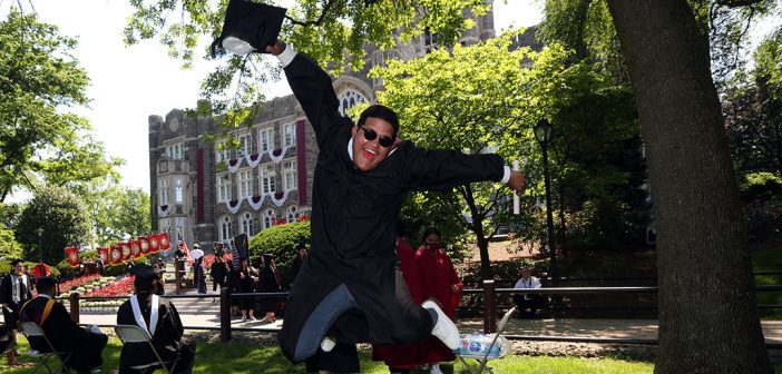 A graduate leaps into the air on Edwards Parade