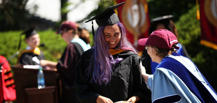 A female graduate with purple haair accepts her dimpoma