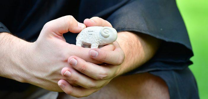 Closeup of a smell ram statue in a graduates' hands