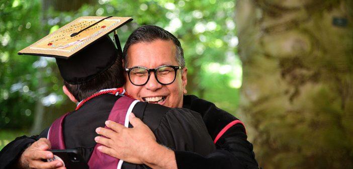 Tito Cruz gives a student a hug