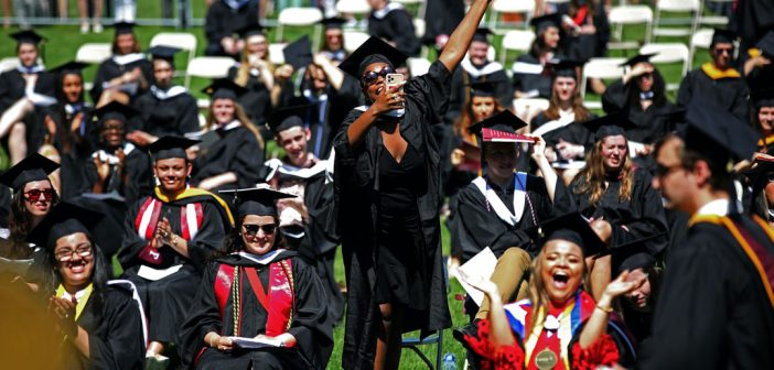 A woman wearing a black graduation gown stands, laughs, and holds up her phone to take a photo, while dozens of graduates around her sit and smile.