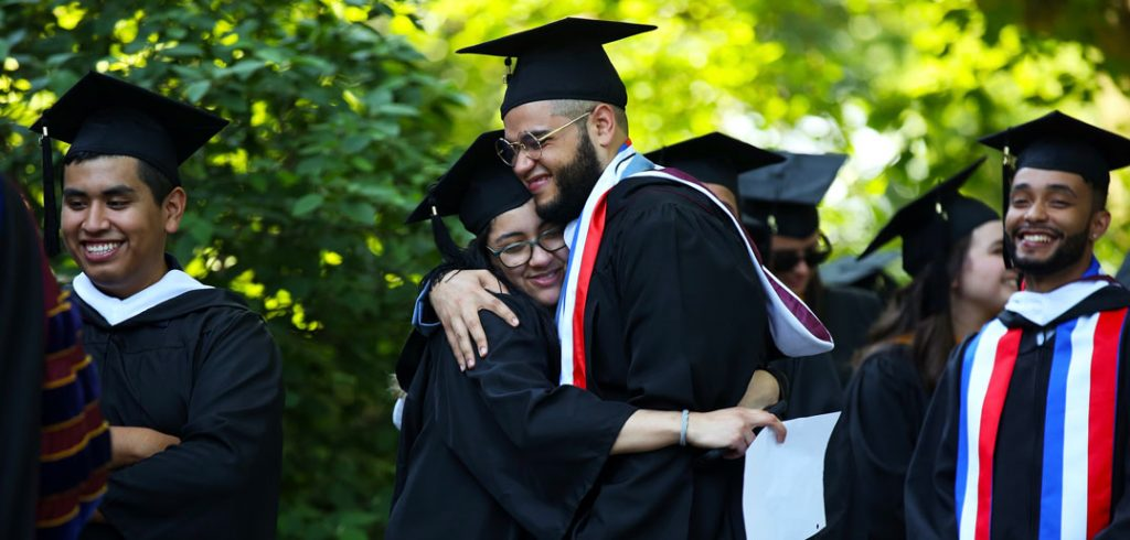 A woman and a man wearing black graduation gowns embrace.