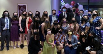 Twenty-four students wearing masks and formal attire smile for a group photo in an indoor setting.