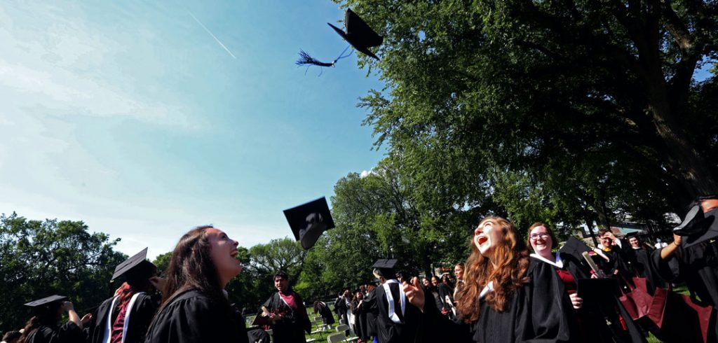 Students wearing black graduation gowns watch a black graduation cap being tossed into the sky.
