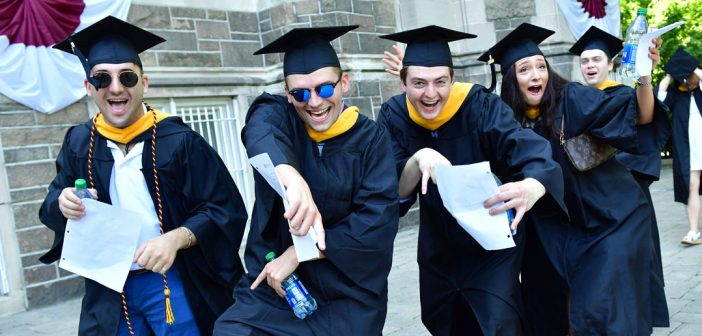 Four students wearing black graduation gowns make silly poses and point at the camera.