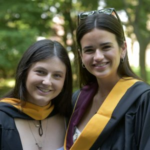 Two women wearing black graduation gowns smile.