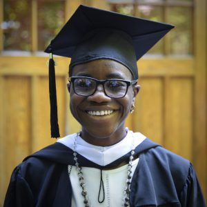 A woman wearing glasses and a black graduation cap smiles at the camera.