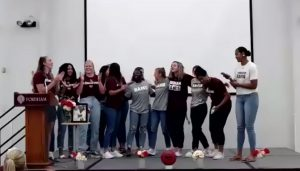 members of the women's basketball team standing together onstage