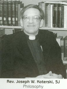 A man wearing glasses and a black Jesuit outfit smiles at the camera.