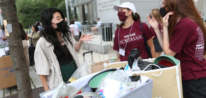 Student outside LC with her belongings and move-in volunteers