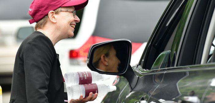 FCRH Dean Maura Mast in baseball cap talking to camily in car