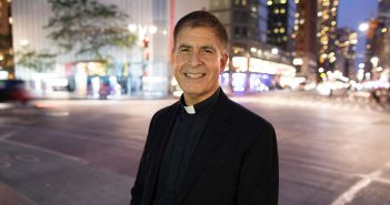Father John Cecero in Columbus Circle at dusk, with streetlights