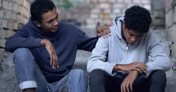 Afro-american teenager trying to make peace with friend, helping boy in need