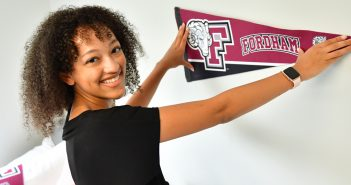 woman student posting Fordham bannner on wall