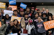 A group of young adults wearing winter coats and holding colorful signs smile for the camera.
