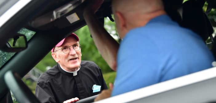 Father McShane talking to man in car
