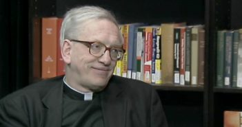 An elderly man wearing a black Jesuit shirt and glasses smiles in front of a bookshelf.