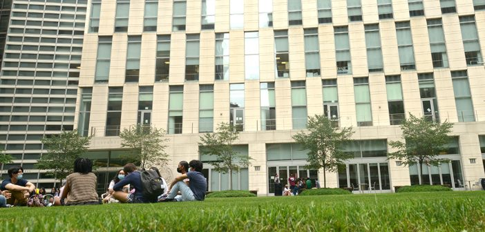 students sit in front of law school