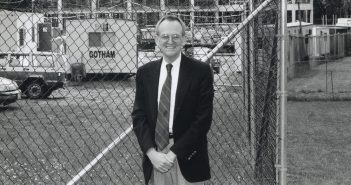 A black and white photo of an elderly man smiling in front of a construction site