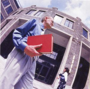A man holding a red book in front of a large Gothic style building
