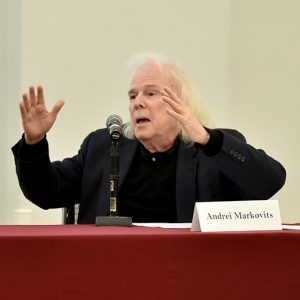 A man with white hair and a black jacket throws his arms up.
