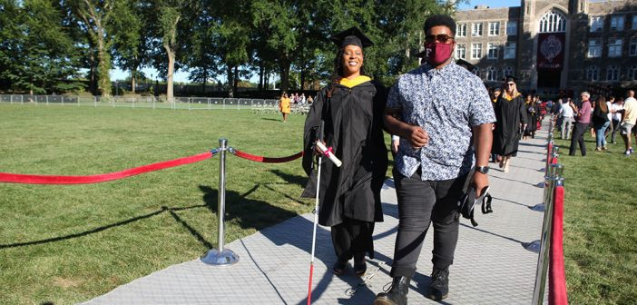 A blind graduate is helped down the aisle by a friend.