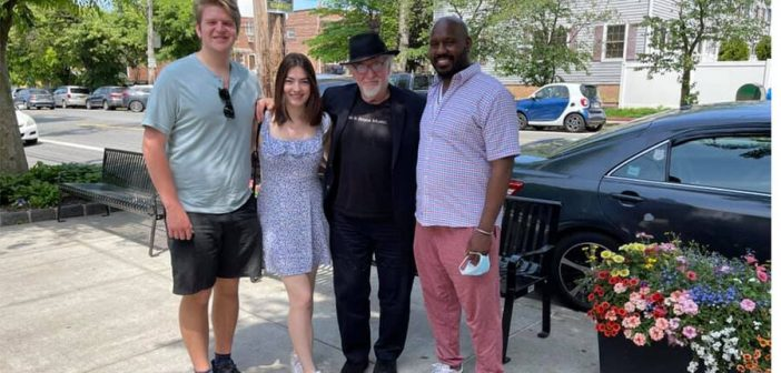 Fordham students Carlos Rico (left) and Alison Rini, who helped launch the Bronx COVID-19 Oral History Project, stand with Professor Mark Naison, the project's faculty adviser, and Lionel Spencer (right), an artist interviewed for the project, outside the Crab Shanty Restaurant on City Island in the Bronx on May 20, 2021.