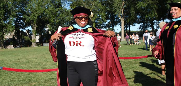 """Woman graduate showing off a shirt under her gown that says """"Dr."""""""