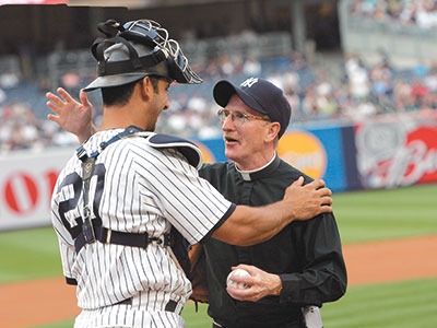 Father McShane blessed Yankees catcher Jorge Posada after throwing out the ceremonial first pitch at Yankee Stadium on July 1, 2009, in honor of the 150th anniversary of Fordham baseball. Photo by Bruce Gilbert
