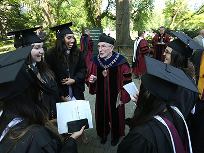 Father McShane speaks with members of the Fordham College at Rose Hill Class of 2020 at their diploma ceremony on June 6, 2021. Photo by Bruce Gilbert