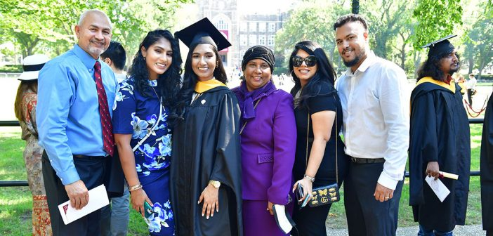 A graduate poses with her family for a picture