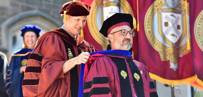 A PhD candidate recieves his academic hood from another man behind him.