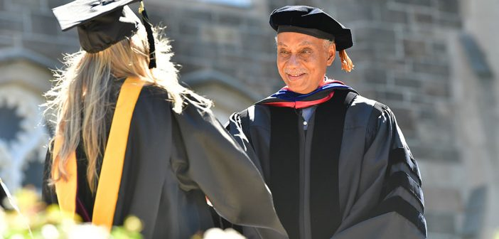 A graduate greets Tyler Stovall, Dean of the Graduate School of Arts and Science