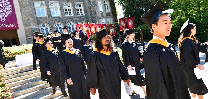 Graduates walk in line down the steps of Keating Terrace.
