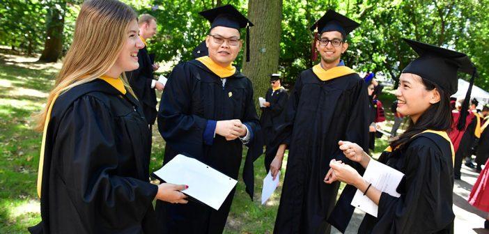 Graduates stand together talking.