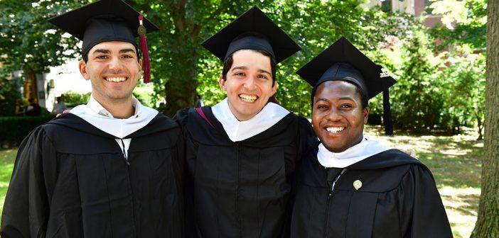 Three male graduates pose for a picture.