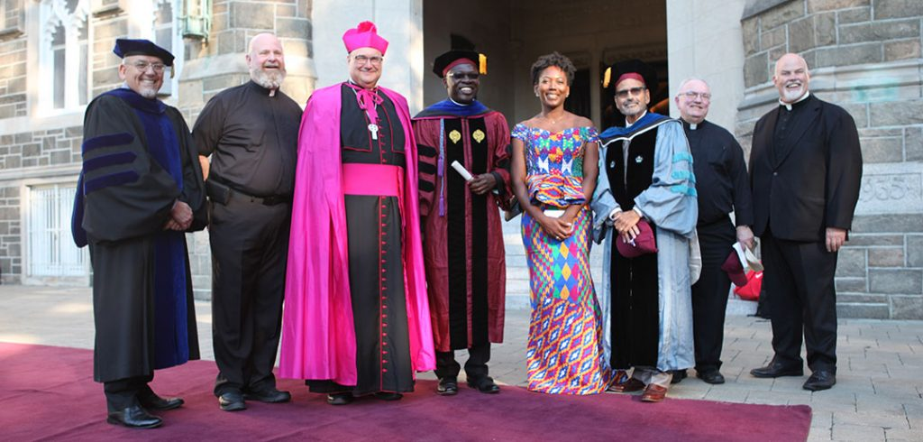 Monsignor Richard G. Henning, Auxiliary Bishop of Diocese of Rockville Centre, standing with a group, including two doctoral students, Collins Adutwum, Ph.D., and Valerie Serpe, Ph.D.