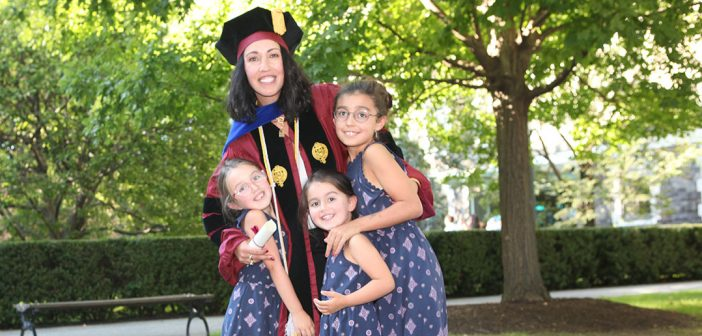 Woman graduate smiling with three children