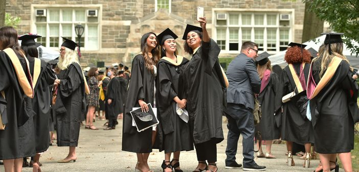 Three graduates look up at a phone posing for a selfie
