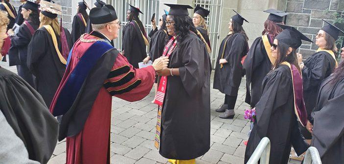 Father McShane greats a graduate as she walks along Keating Terrace