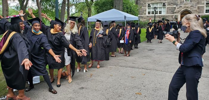 Group of women graduates lean forward with outstretched arms to pose for a picture