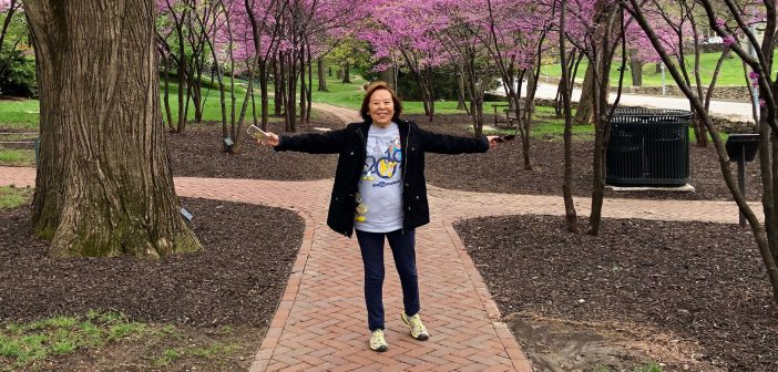 An elderly woman of Asian descent smiles and stands in front of a group of trees with pink blossoms while throwing out her arms.